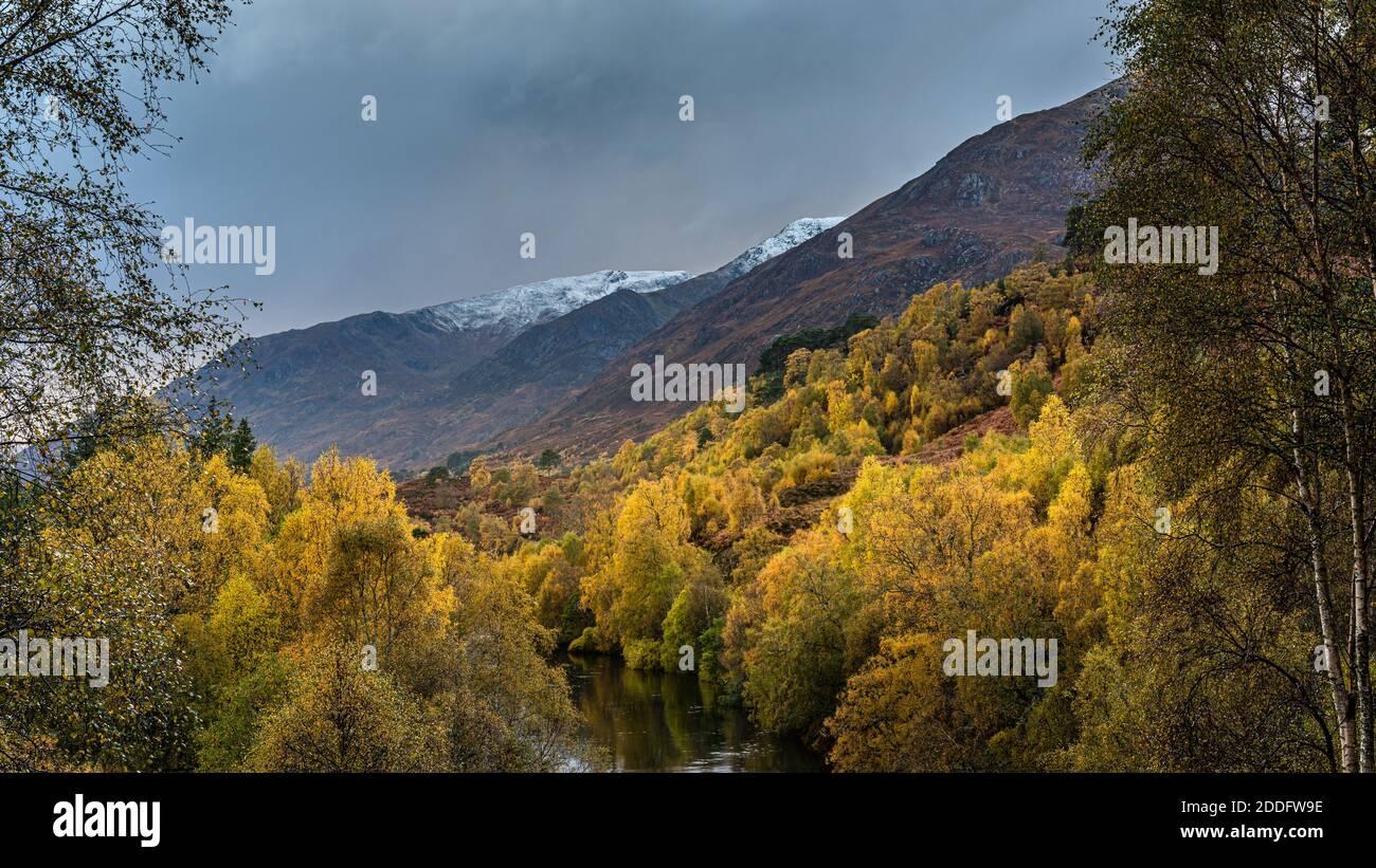 Los colores de otoño en Glen Affric en las tierras altas de Escocia con las primeras nieves en las colinas Foto de stock