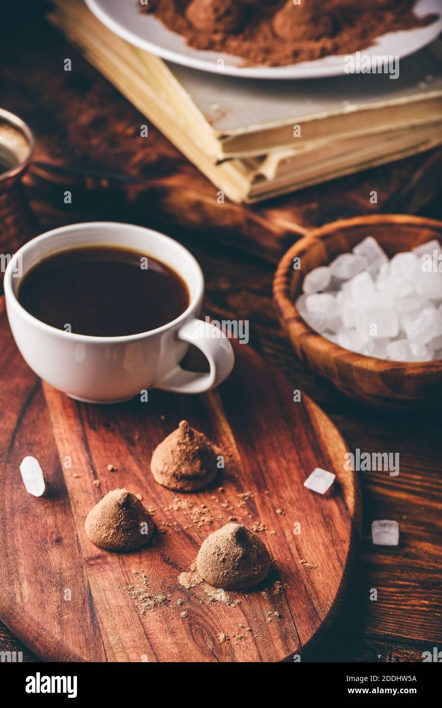 Trufas de chocolate recubiertas de cacao en polvo con café negro Foto de stock
