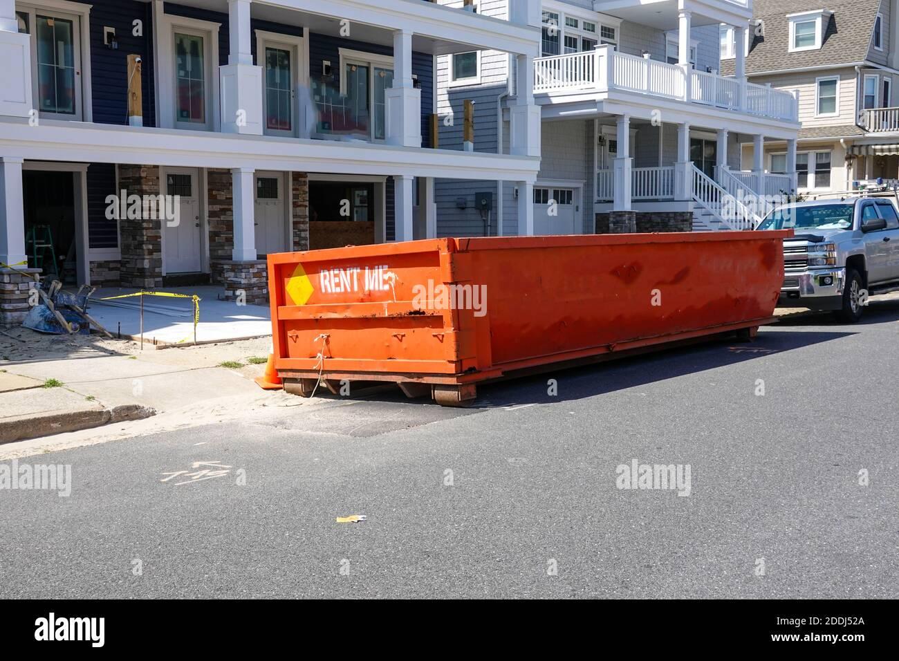 El final de un contenedor de naranja visto en una calle delante de un camión en un sitio de construcción en un día soleado Foto de stock