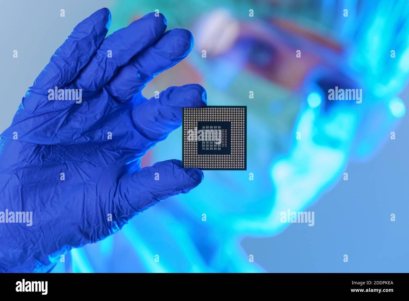 Un ingeniero que trabaja en un laboratorio, vistiendo un uniforme especial y guantes protectores mantiene el nuevo procesador en manos y examina Foto de stock