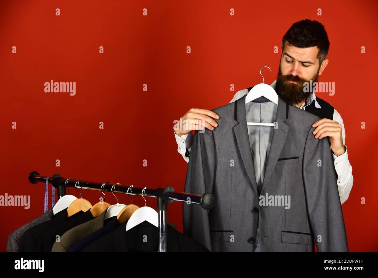 El hombre de cintura baja con barba está cerca del estante con ropa contra el fondo rojo. El chico con cara seria sostiene la chaqueta gris en la percha de la ropa y la mira. El hombre busca ropa en la tienda de moda Foto de stock