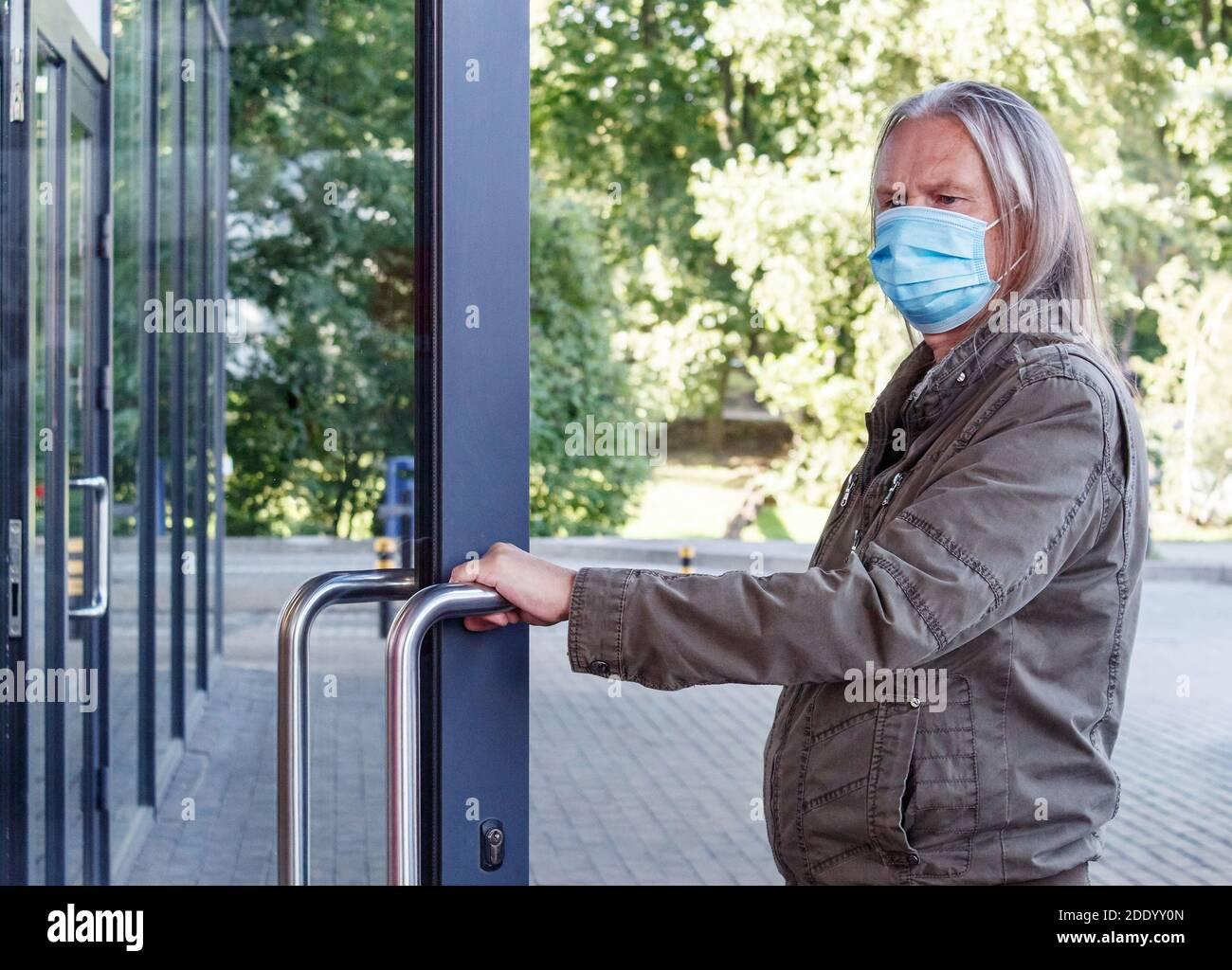 el anciano con máscara protectora abre la puerta del tienda al aire libre el día de otoño Foto de stock