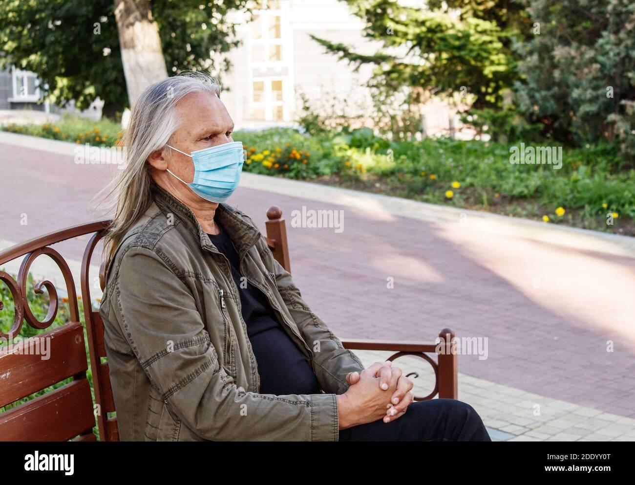 el hombre mayor con mascarilla protectora se sienta en un banco un parque de la ciudad en el soleado día de otoño Foto de stock