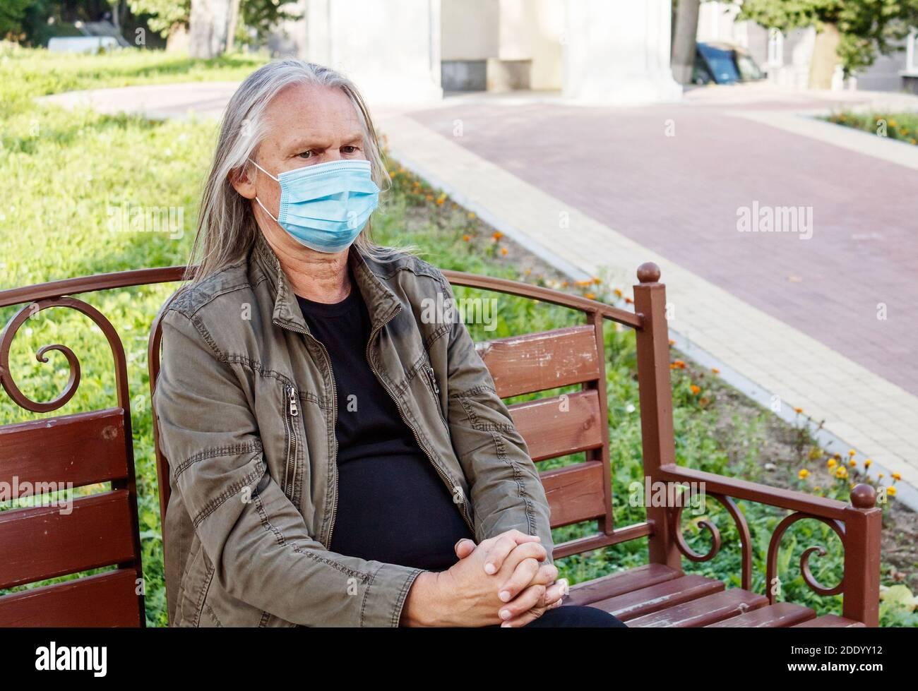el anciano con pelo largo gris en máscara protectora se sienta en un banco en un parque de la ciudad en otoño soleado día Foto de stock