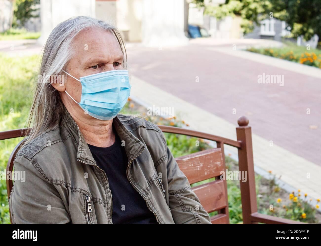 retrato de anciano con pelo largo gris en protector máscara se sienta en un banco en un parque de la ciudad en soleado día de otoño Foto de stock