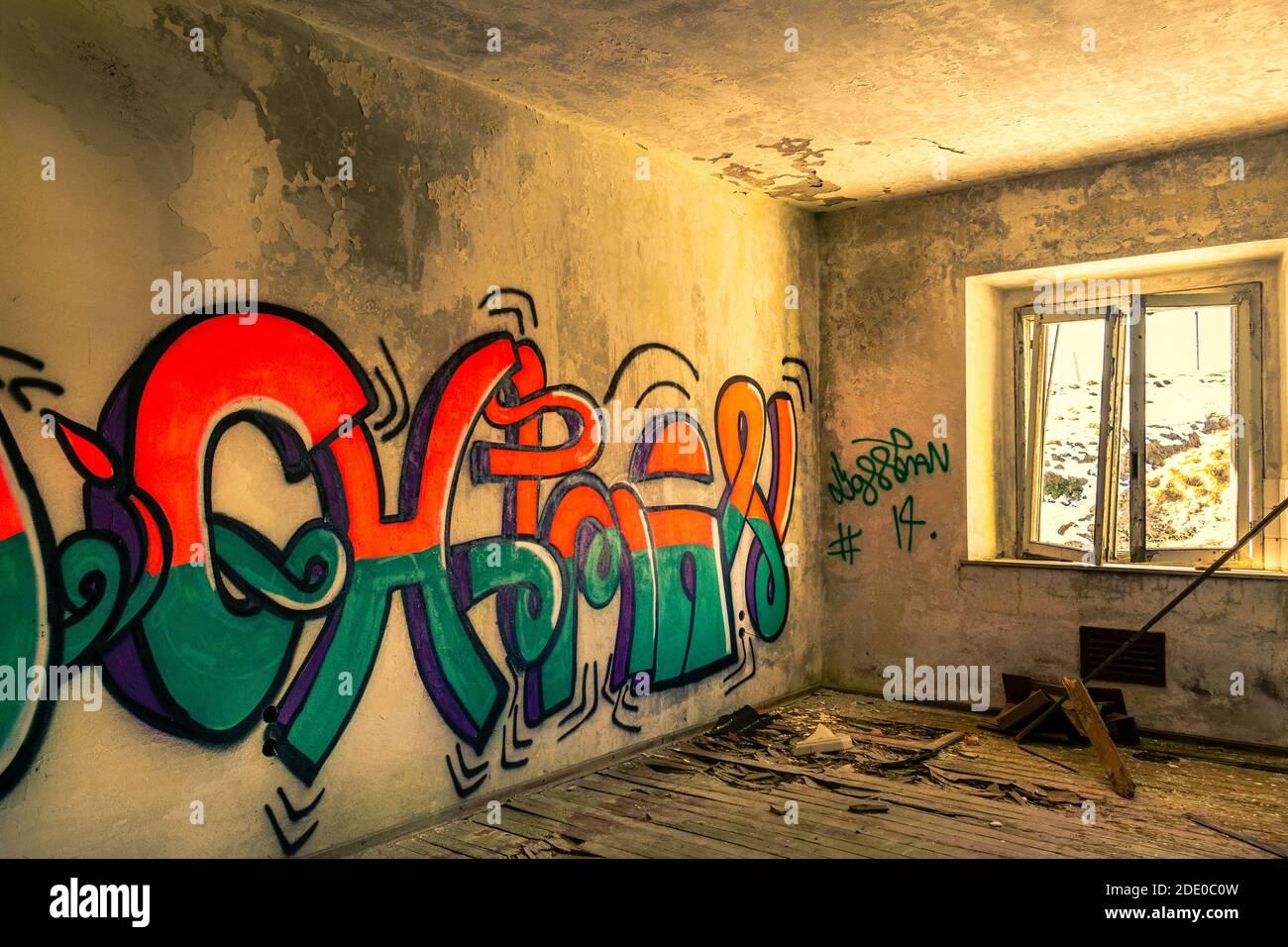 Habitación desbocada con ventana rota, suelo de madera destruido, paredes de graffiti multicolores. Interior de edificio abandonado. Monte Grappa, Vicenza, Italia Foto de stock