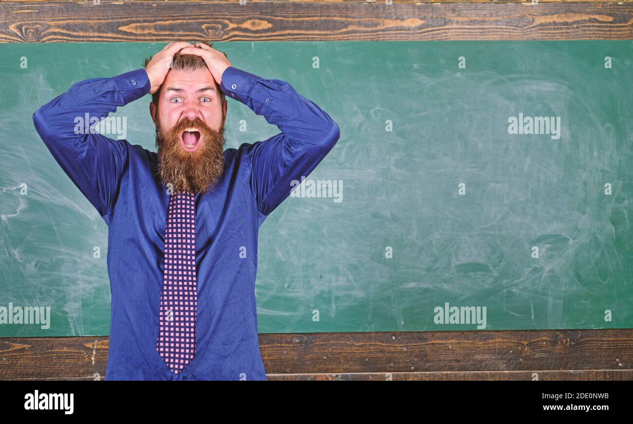 El hombre barbudo maestro o educador tienen fondo de la pizarra principal. Preste atención a su comportamiento y modales. Etiqueta de los maestros consejos profesionales de la educación moderna. El maestro se comporta de manera poco profesional. Foto de stock