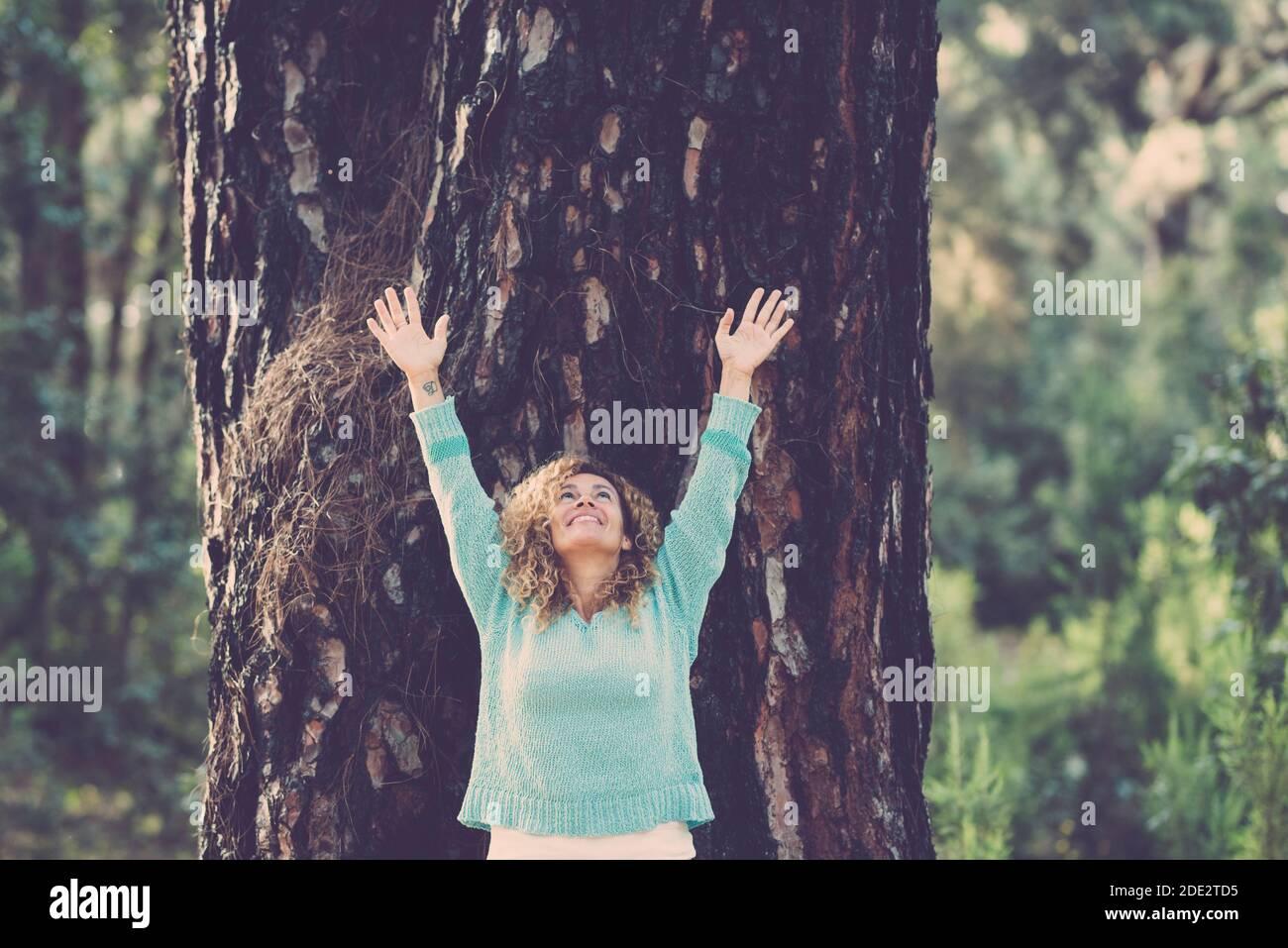 Alegre bonita mujer de pie con un gran tronco de árbol fondo - abrazando el estilo de vida al aire libre y salvar la madera del bosque conpewpt - el día de la tierra celebrab Foto de stock