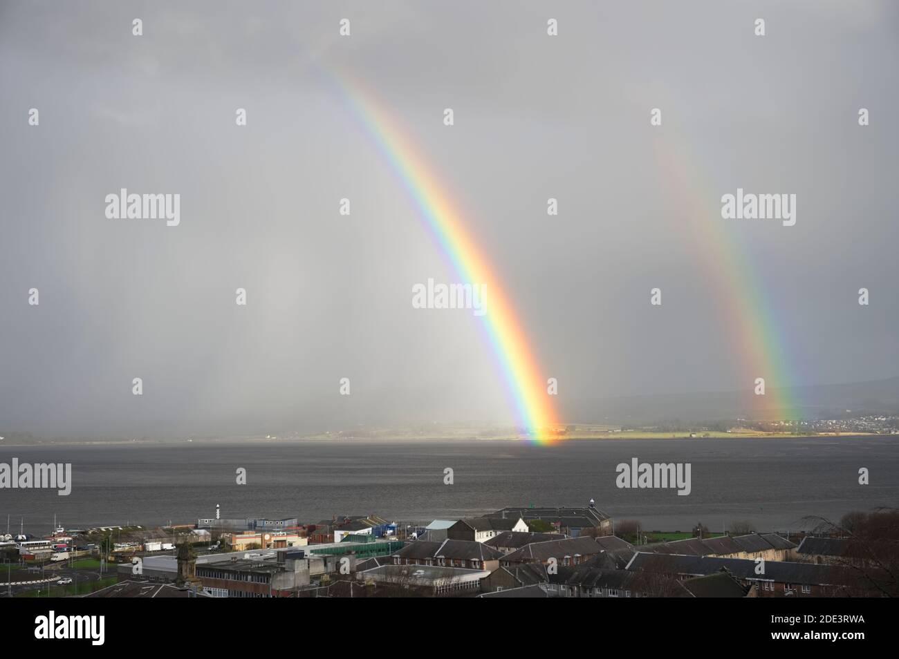 Arco iris brillante alto en el cielo sobre el mar durante la oscuridad tormenta Foto de stock