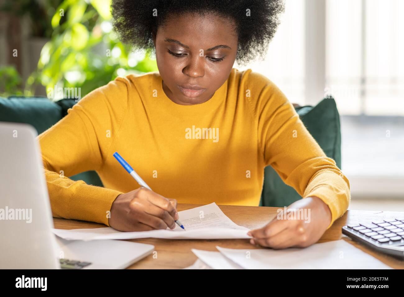 Mujer negra empleada o gerente de trabajo remoto en casa durante el cierre, toma notas con el lápiz, trabaja con documentos en papel. Trabajador de oficina durante una pande Foto de stock