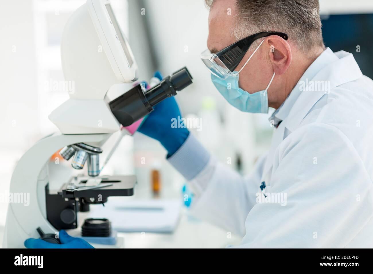 microbiólogo un científico mirando a través de un microscopio. Foto de stock