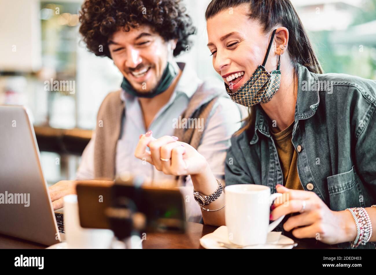 Jóvenes influencers mileniales compartiendo contenido creativo en la plataforma de streaming - Concepto de marketing moderno con pareja de próxima generación que se divierte Foto de stock