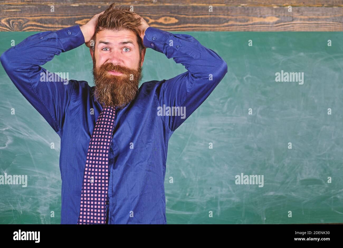 Etiqueta de los maestros consejos profesionales de la educación moderna. El hombre barbudo maestro o educador tienen fondo de la pizarra principal. El maestro se comporta de manera poco profesional. Preste atención a su comportamiento y modales. Foto de stock