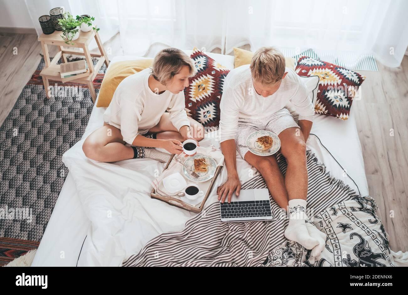 Los adolescentes se unen en pijamas en una cama acogedora navegando por Internet usando un ordenador portátil y tomando un café por la mañana con postre pastel de manzana. Parejas relaciones an Foto de stock