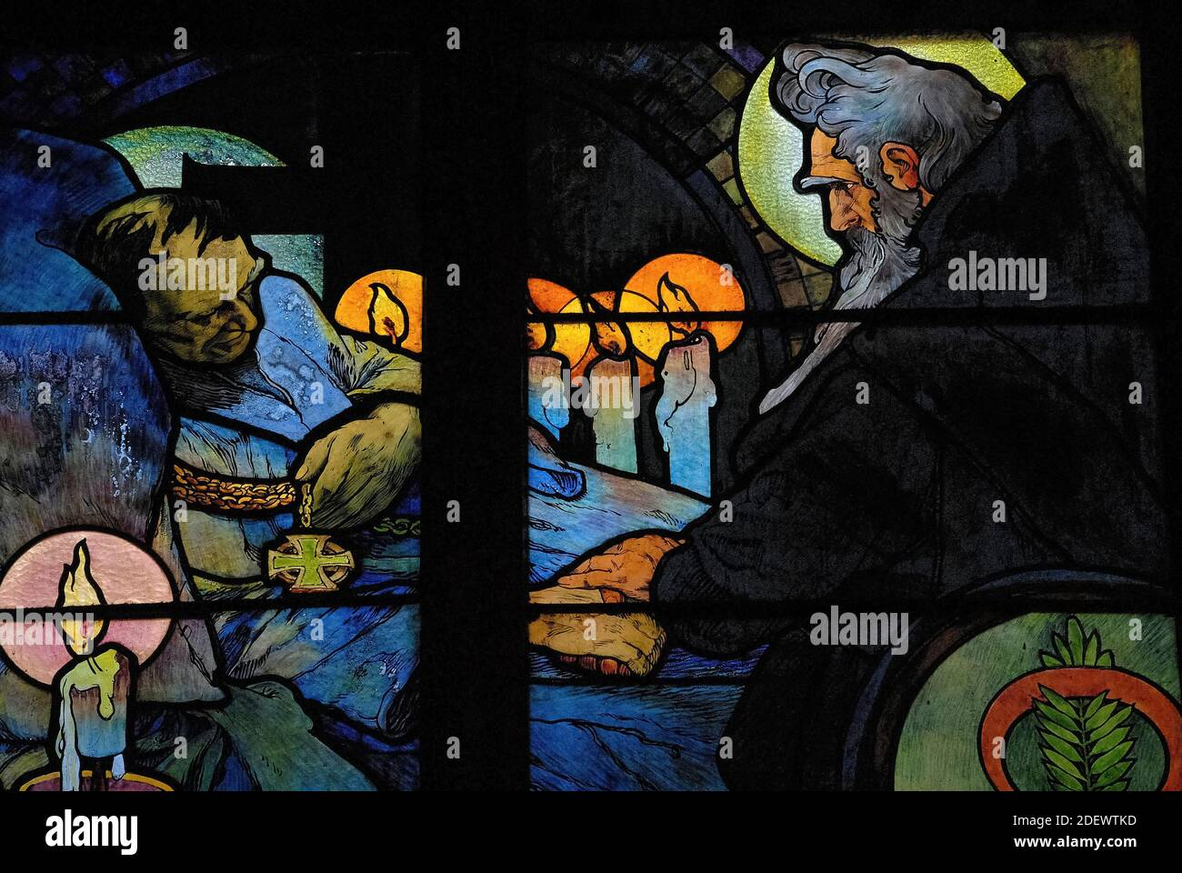Vigilia a la luz de las velas por el lecho de muerte del teólogo bizantino y misionero San Cirilo, representado por el influyente artista Art Nouveau Alphonse Mucha en su vívida vidriera de 1930 para la Capilla del Nuevo Arzobispo en la Catedral de San Vito en Praga, capital de la República Checa / República Checa. La obra de arte, una alegoría de Cristo que bendice a las naciones eslavas, presenta escenas de la vida de los 'Apóstoles a los eslavos' Cirilo y su hermano Metodio, así como el patrón checo san Wenceslao, duque de Bohemia, y su abuela, San Ludmila. Foto de stock