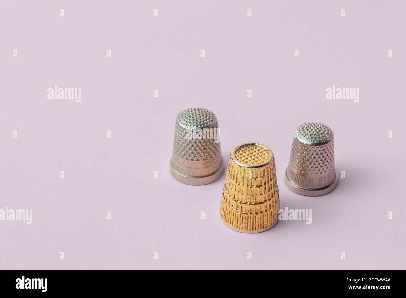 Composición triangular de tres dedales, dos tipos, y un oro sobre fondo rosa. Artículos de costura. Foto de stock