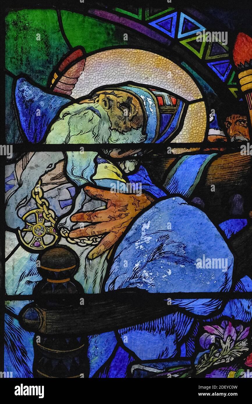 El luto coloca el reconfortante brazo alrededor de los hombros del agonizante teólogo bizantino y misionero San Metodio (815-885 DC), en vívido 1930 vidrieras del influyente artista Art Nouveau Alphonse Mucha en la capilla del nuevo arzobispo de la Catedral de San Vito en Praga, capital de la República Checa / República Checa. La ventana completa, una alegoría de Cristo que bendice a las naciones eslavas, presenta escenas de la vida de los 'Apóstoles a los eslavos' Metodio y su hermano Cirilo, así como el patrón checo san Wenceslao, Duque de Bohemia, y su abuela, San Ludmila. Foto de stock