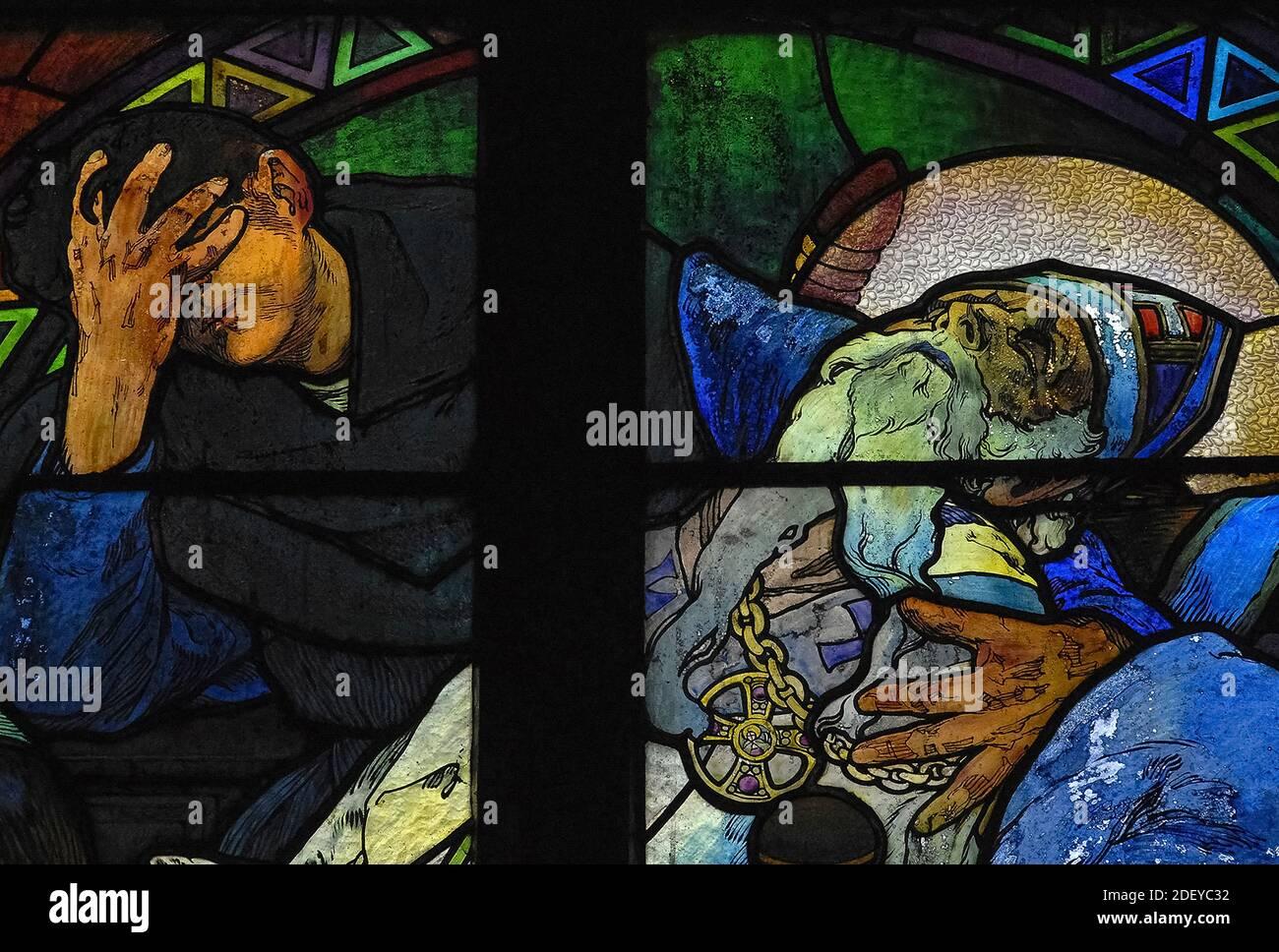 El luto penoso cubre los ojos mientras coloca el reconfortante brazo alrededor de los hombros del agonizante teólogo bizantino y misionero San Metodio (815-885 DC), en vívido 1930 vidrieras del influyente artista Art Nouveau Alphonse Mucha en la capilla del nuevo arzobispo de la catedral de San Vito en Praga, capital de la República Checa. La ventana completa, una alegoría de Cristo que bendice a las naciones eslavas, presenta escenas de la vida de los 'Apóstoles a los eslavos' Metodio y su hermano Cirilo, así como el patrón checo san Wenceslao, Duque de Bohemia, y su abuela, San Ludmila. Foto de stock