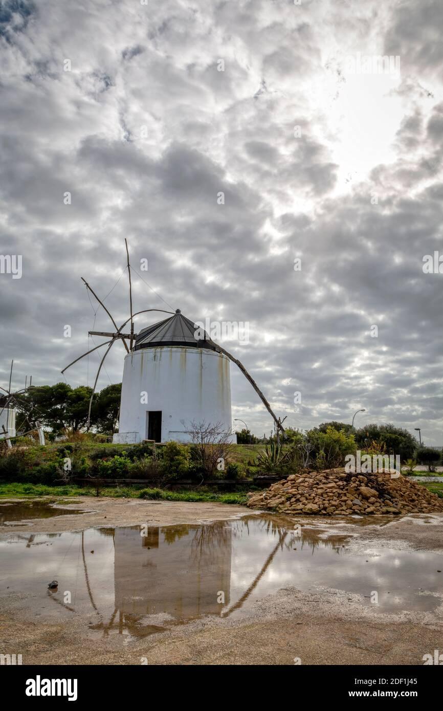 Molino de viento que se refleja en un charco con un espectacular cielo adentro el fondo Foto de stock