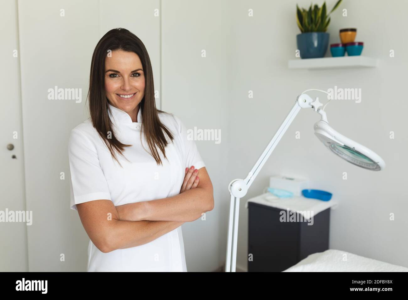 Retrato de la mujer caucásica esteticista de pie en un salón de belleza, mirando a la cámara y sonriente Foto de stock