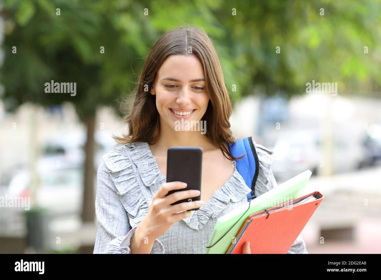 Vista frontal retrato de un estudiante feliz caminando comprobar inteligente teléfono en la calle Foto de stock