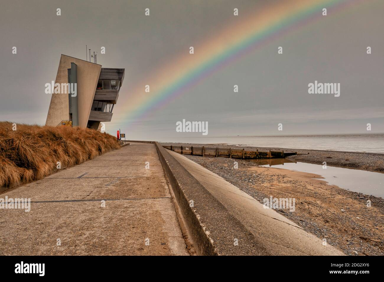 Rainbow at Rossall Beach, Fleetwood, Lancashire, Reino Unido. El edificio de cuatro pisos en el paseo exterior en Rossall Point es Rossall Coastwatch Tower. Foto de stock