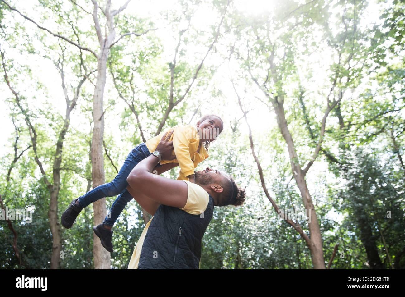 Juguetón padre sin preocupaciones levantando a hija debajo de los árboles en el parque soleado Foto de stock