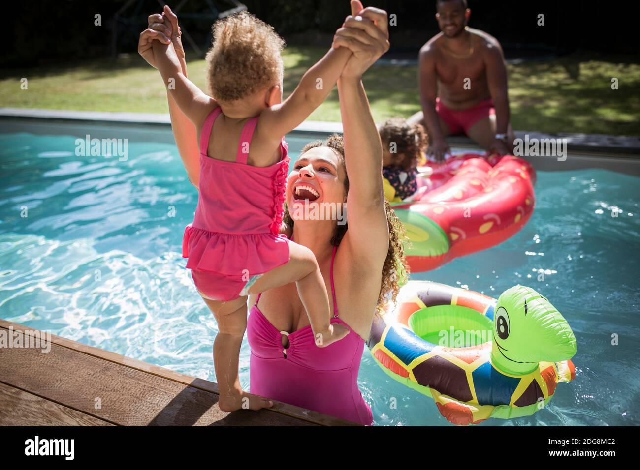 Madre juguetona levantando a su hija pequeña en la piscina soleada Foto de stock