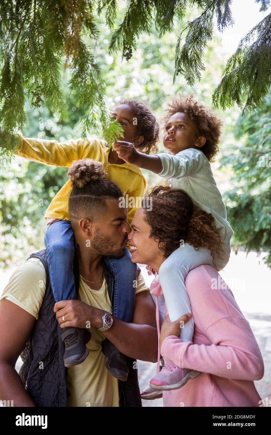 Una pareja cariñosa que lleva hijas sobre los hombros debajo de los árboles del parque Foto de stock