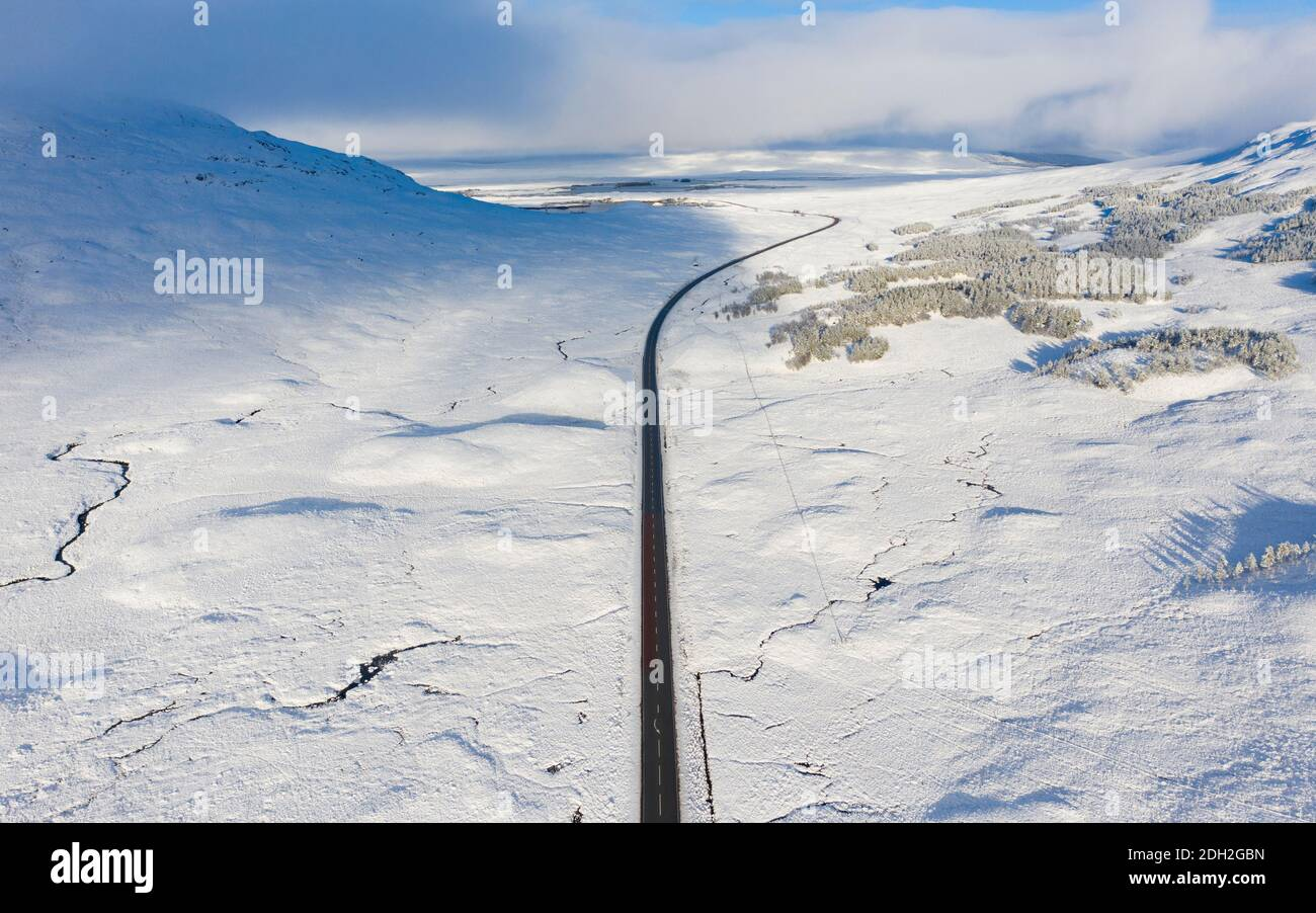 Vista aérea de la carretera A82 cruzando Rannoch Moor cubierto de nieve durante el invierno, Highlands, Escocia, Reino Unido Foto de stock