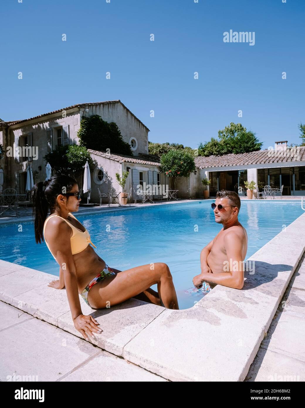 Pareja relajándose en la piscina en la Provenza Francia, hombres y mujeres relajándose en la piscina en el complejo de lujo Foto de stock
