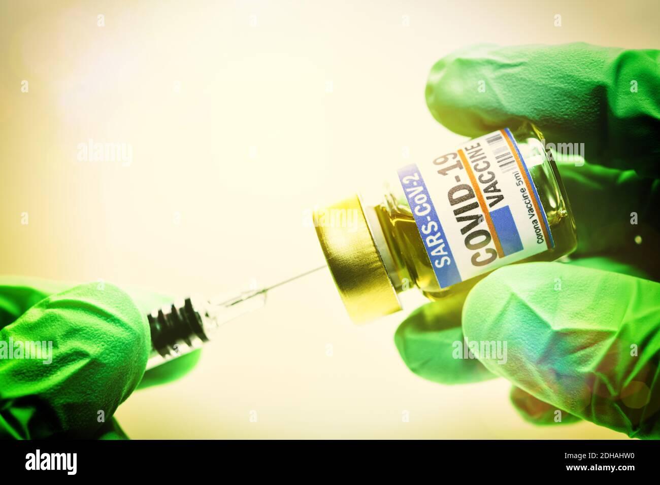 Hände in Schutzhandschuhen halten Injektionsfläschchen mit Corona-Impfstoff und Impfspritze, Symbolfoto Corona-Impfmittel Foto de stock