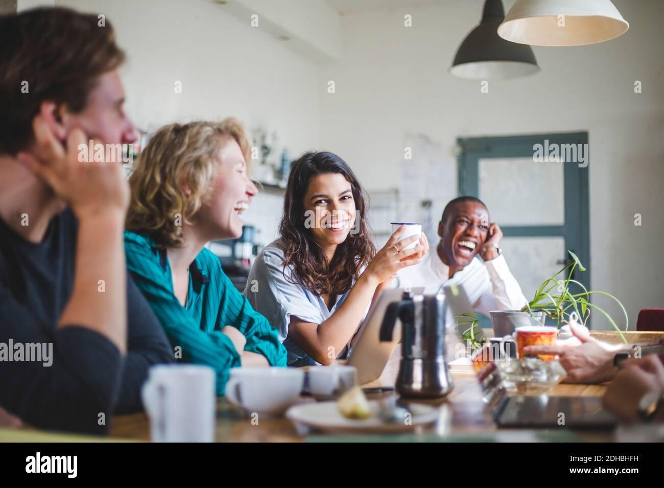 Retrato de alegre joven programador de computadoras sentado con hackers en la mesa en la oficina creativa Foto de stock