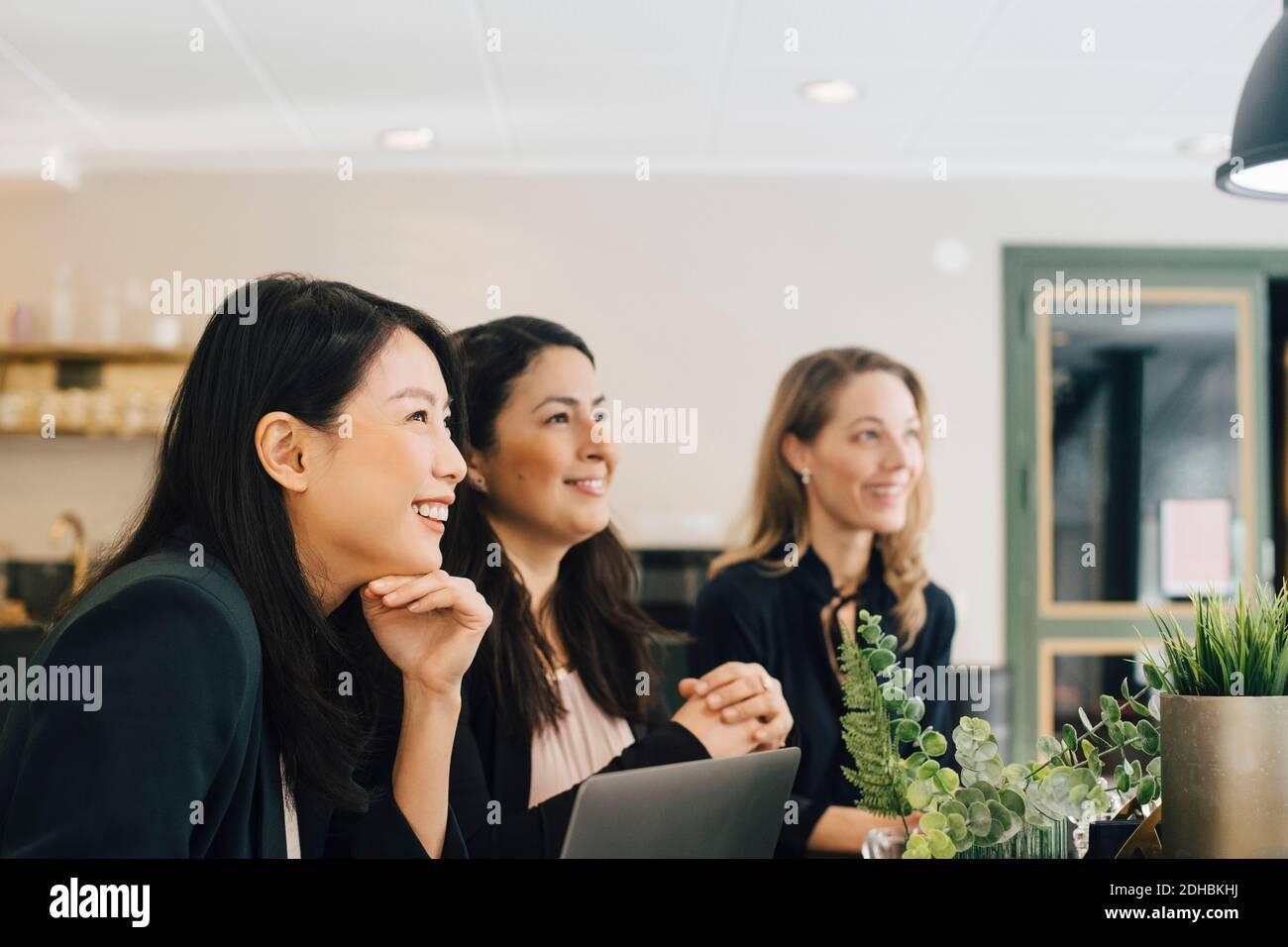 Mujeres de negocios sonriendo sentadas en la mesa de conferencias en la reunión Foto de stock