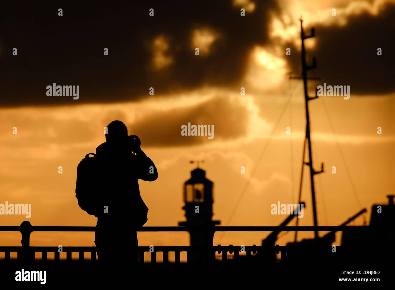 Un fotógrafo captura la calma antes de la tormenta Alex, mientras el sol se levanta detrás del faro del puerto de Penzance el primer día de octubre. Foto de stock