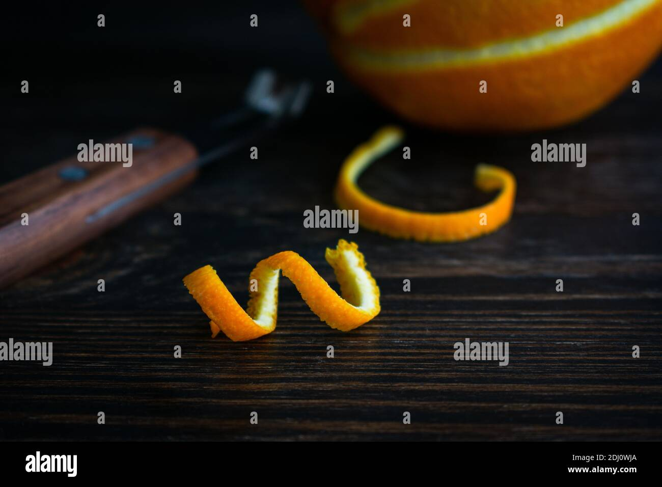 Torcedura de naranja sobre un fondo de madera de la Marca: Una tira fresca de la cáscara de naranja y un cuchillo del canal Foto de stock