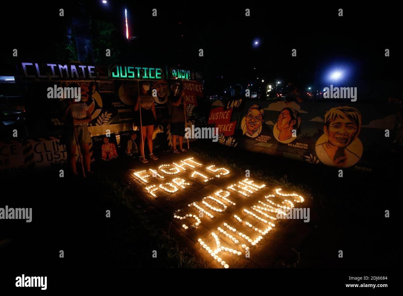 Activistas del clima encendieron velas y llevaron a cabo banderas de iluminación LED el 11 de diciembre de 2020. Esta actividad conmemora el quinto aniversario del Acuerdo de París con un llamado a luchar para 1.5 y a poner fin a la matanza de defensores del medio ambiente. Ciudad de Quezon, Filipinas. Foto de stock