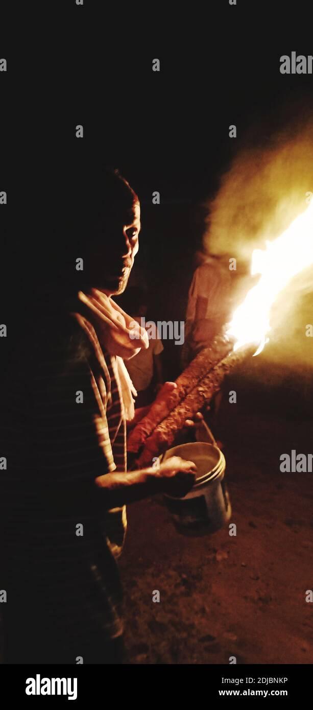 Vista lateral del hombre maduro que sostiene fuego mientras que está parado contra el cielo en la noche Foto de stock