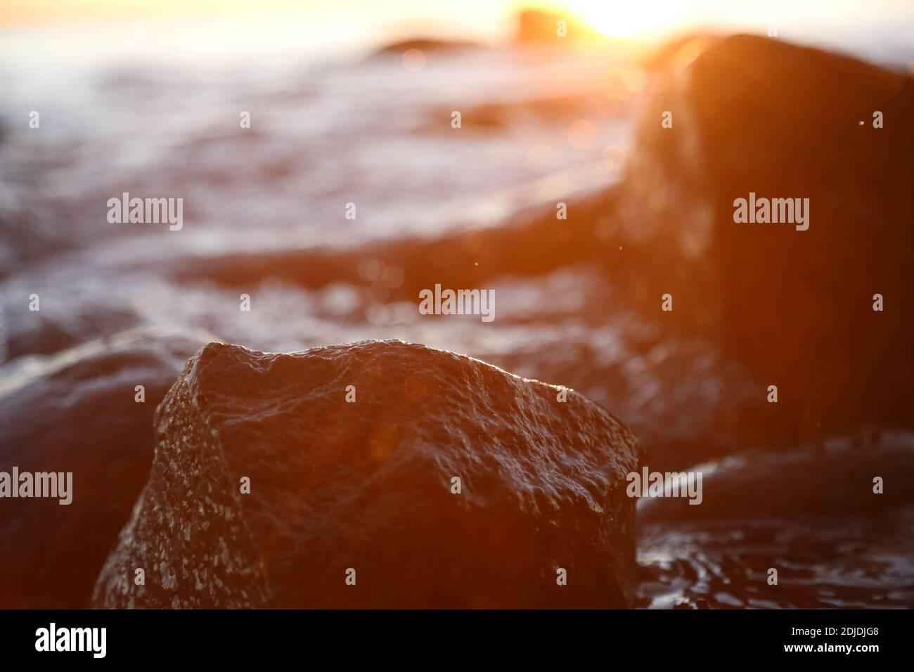 Piedras y rocas de Stony Beach iluminadas por el sol en el primer plano de la tarde, Texture Sunset y Sunrise Foto de stock
