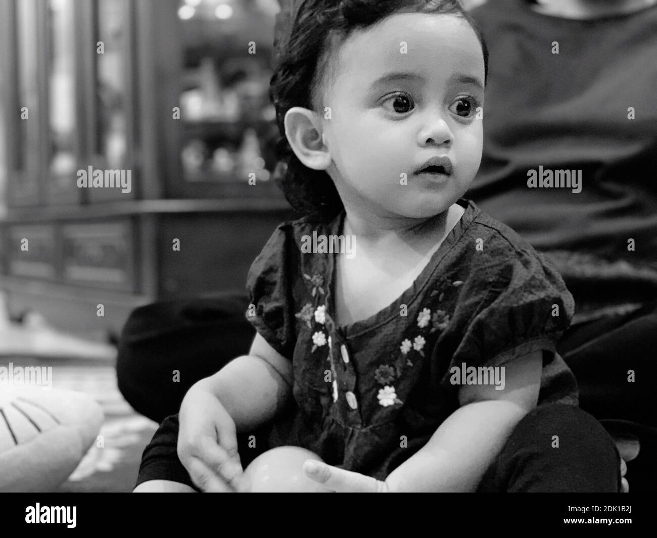 Chica linda mirando lejos mientras se sienta en casa Foto de stock