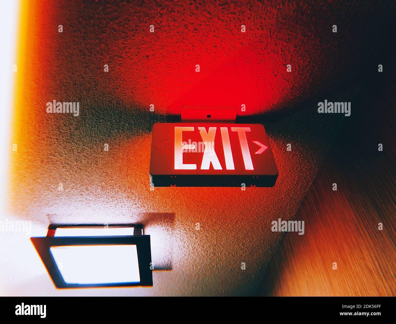 Ángulo de visión baja de señal de salida iluminada en el techo Foto de stock