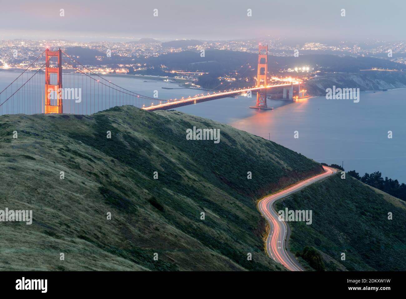 Senderos de luz para coches y el puente Golden Gate Glowing por la noche Foto de stock