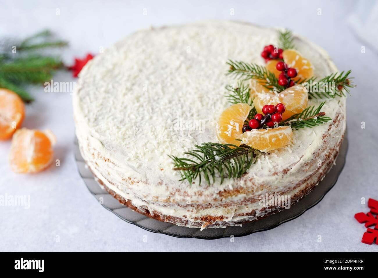 Comida de Navidad pastel de fruta, cubierto de verdor de invierno, bayas decorativas y tangerinas Foto de stock