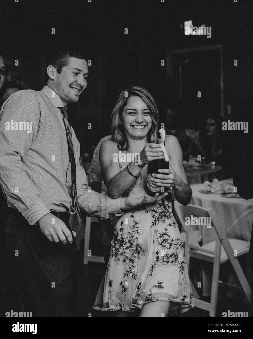Champaña de apertura para una pareja feliz en el restaurante Foto de stock