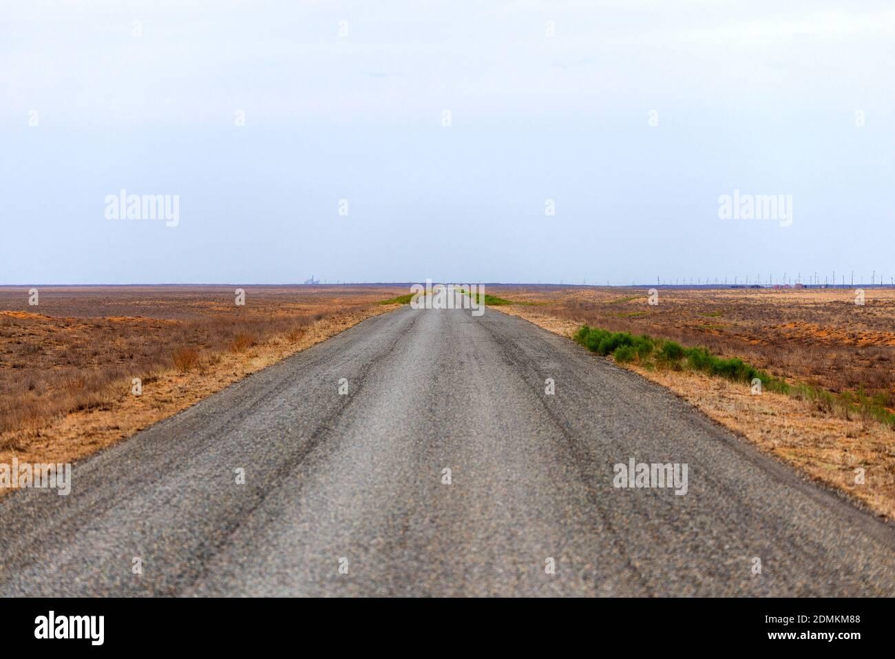 Largo camino que se extiende a la distancia en la estepa. Foto de stock