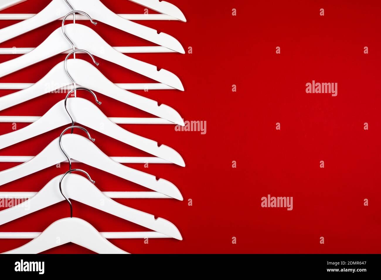 Imagen en color horizontal con vista frontal de perchas blancas sobre fondo rojo. Concepto de venta de ropa. Foto de stock