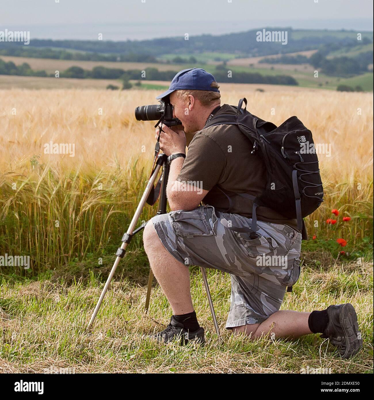 Hombre fotógrafo arrodillado por un campo de cebada mirando a través de su cámara montada en un trípode. Paisaje de formato cuadrado con colinas en el fondo. Foto de stock