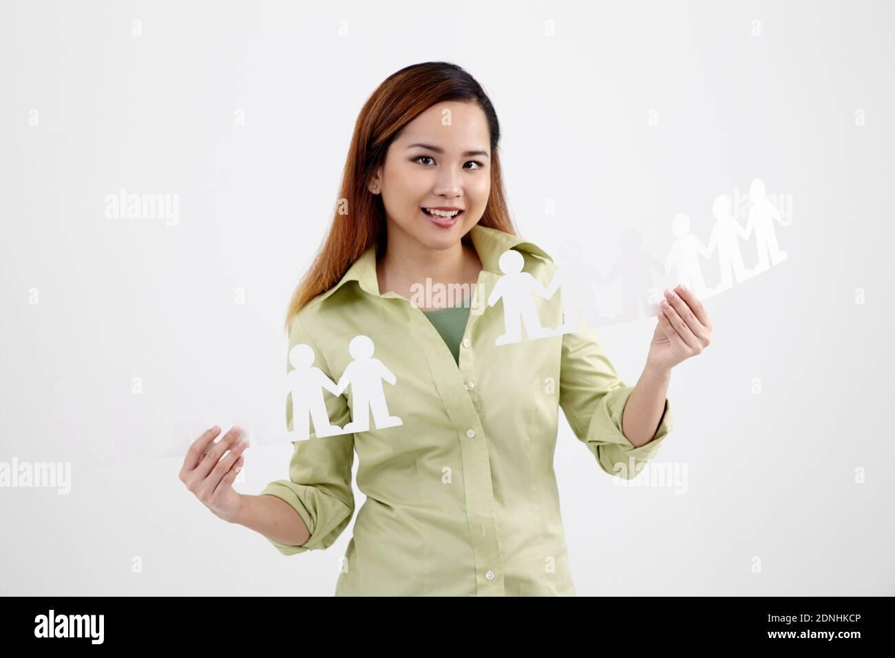 Retrato de la joven feliz sosteniendo cadenas de papel de la gente contra fondo blanco Foto de stock