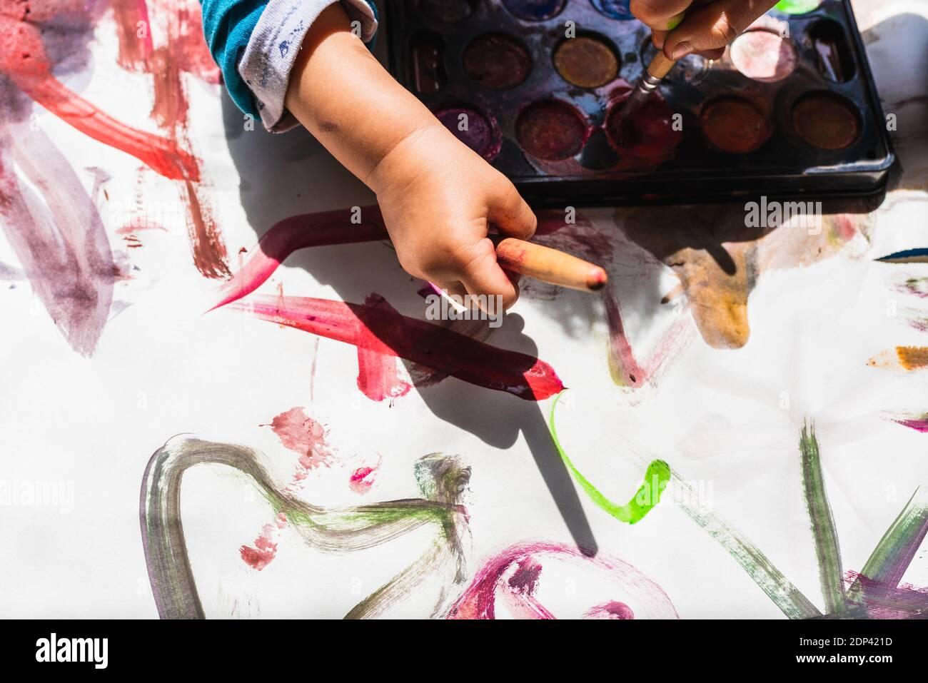La niña creativa pinta en el suelo con la pintura de los niños un dibujo abstracto de los bebés sin formas. Foto de stock