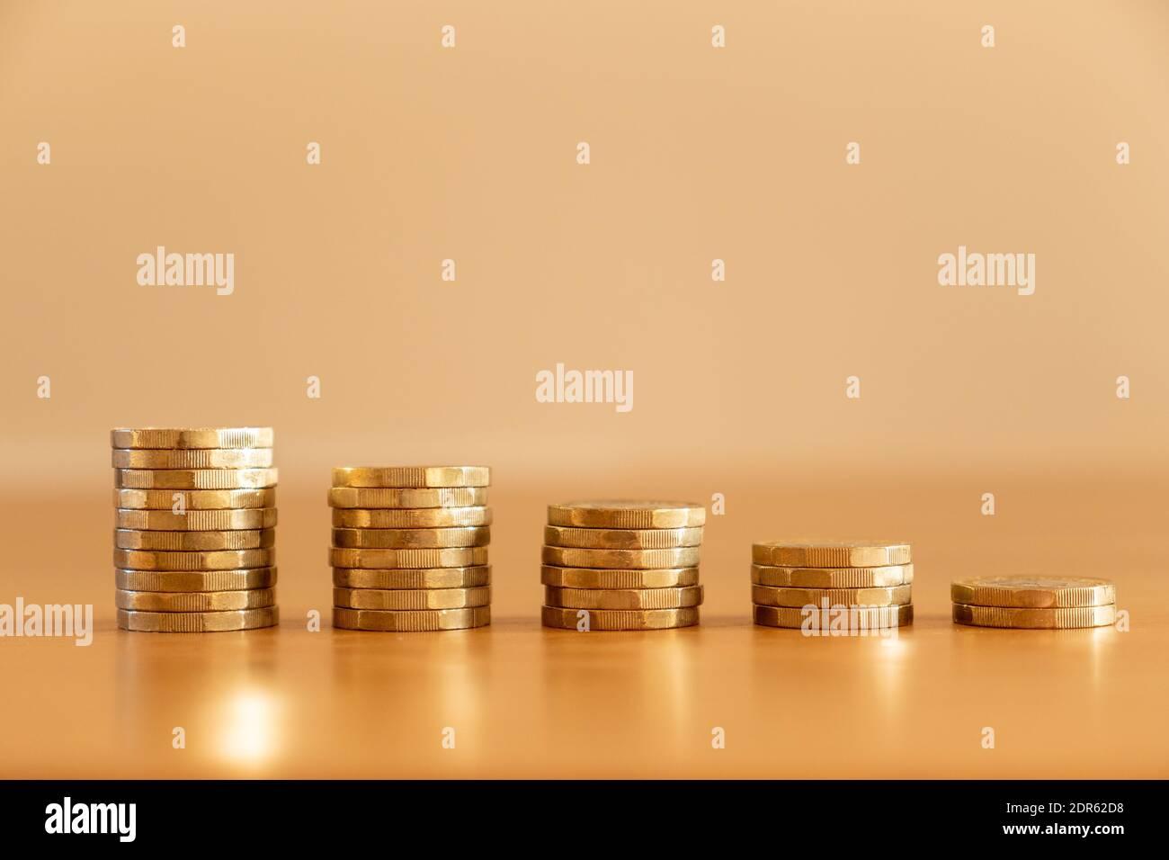 Primer plano de pilas de muchas monedas de una libra GBP que disminuyen de tamaño como el dinero que baja simbolizando los efectos de la inflación, Reino Unido Foto de stock
